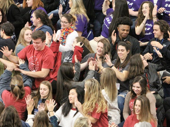 Students race to high five each other while listening to motivational speaker and social media influencer Mike Smith.