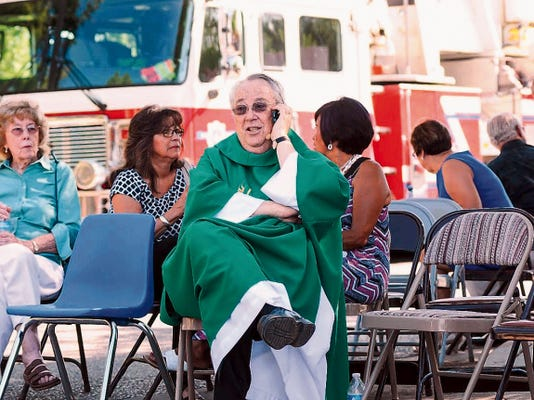 While waiting in a staging area, Holy Cross Catholic Church Monsignor John Anderson tries to get in touch with other local churches to warn them of the two explosions that occurred Sunday morning and to be vigilant.