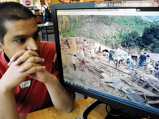 New Mexico State University doctoral student Rishi Sapkota shows a photo of Sipa Pokhare, his village in Nepal after a 7.8-magnitude earthquake destroyed much of it on April 25.