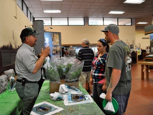 JESSICA ONSUREZ CURRENT-ARGUS   Michael Salmon, of the U.S. Forest Service, gives advice on raising some of the species of trees being gifted to guests at the Living Desert Zoo and Gardens State Park Earth Day celebration Saturday.