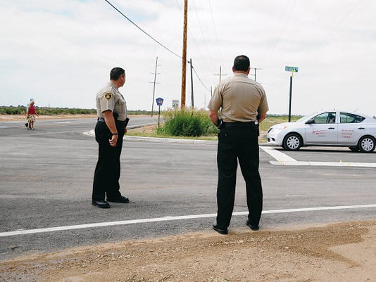 JESSICA ONSUREZ CURRENT-ARGUS   Eddy County Sheriff's Officers Captain Arsenio Jones and Chief Mark Cage watch as the first vehicle to travel the newly reopened intersection at Derrick Road and Old Cavern highway stops at the newly placed stop sign creating a four-way intersection.   Law enforcement will be keeping an eye on the intersection for the next few days as motorists get accustomed to the changes.
