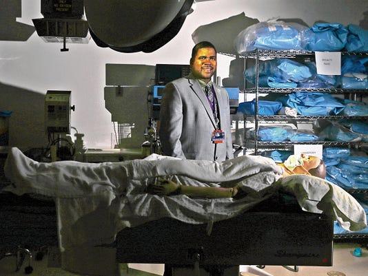 Teddy Farias, dean of the School of Health Sciences, poses Thursday in San Juan College's operating room lab in Farmington.