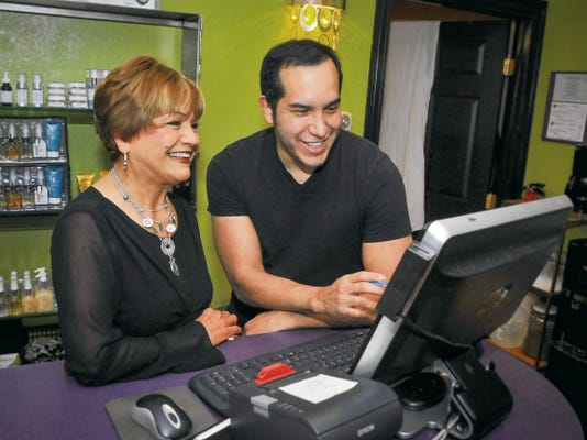 Jett Loe — Sun-News Tencha Carmona, at left, and son Marco Carmona, co-owners of Carmona's Urban Spa & Salon check the day's schedule.