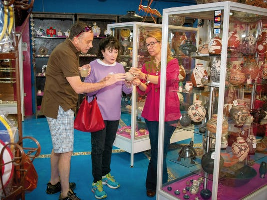 Ivonne Romero, right, shows pottery treasures at The Pink Store in Palomas, Mexico. The famed Borderland emporium and restaurant also offers tours into Mexico to visit artisans in Casas Grandes and Copper Canyon.