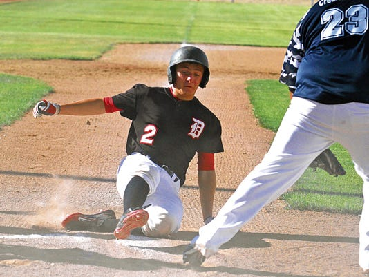 The Demons' Zach Szura (2) slides safely into home plate Tuesday during a game against 4CB at the Farmington Sports Complex.