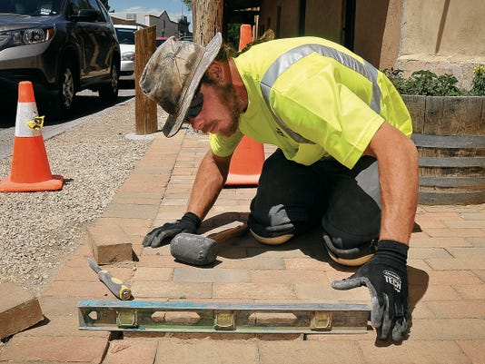 Jett Loe-Sun-News   Gary Garrison, hired by the Town of Mesilla as a part-time bricklayer in September of 2014, repairs a sidewalk near the town plaza on Friday.