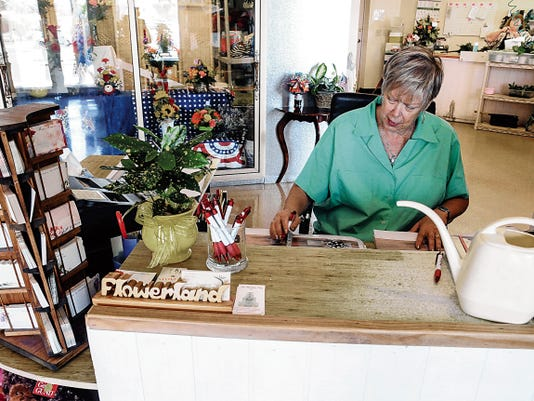 Robin Zielinski - Sun-News   Barb's Flowerland owner Barb Baumann works at her shop in it's new location in suite 126 of the Arroyo Plaza. While the location will continue operation as Barb's, Baumann last week retired and handed over ownership of  the operation she has manned for 15 years.