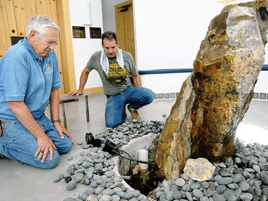Carl McGrew, left, a member of Holy Cross Retreat Center's Good Works Volunteers, works with Javier Melero on a natural stone baptismal font in the Holy Cross Chapel. The stone fountain brings the sounds of nature beloved by the retreat's patron saint, Francis of Assisi.