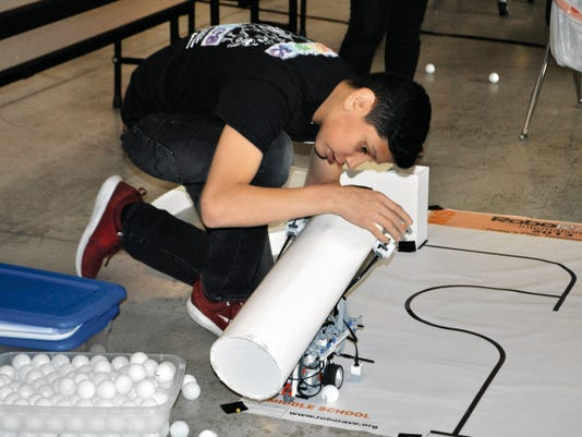 Jorge Medina tries to fit as many ping-pong balls as possible into his robot's delivery system before taking part in the RoboRAVE line following challenge. The more ping-pong balls delivered, the higher the score.