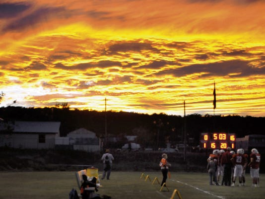 a Fiery sky lights up the night as the Corona football team takes a time out.