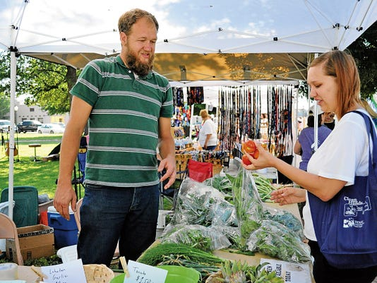 JESSICA ONSUREZ CURRENT-ARGUS   Philip Huston, left, sells fresh produce to to a customer at the Carlsbad MainStreet Farmer's Market Saturday morning.   The market had it's opening day on the lawn of the Eddy County Courthouse.