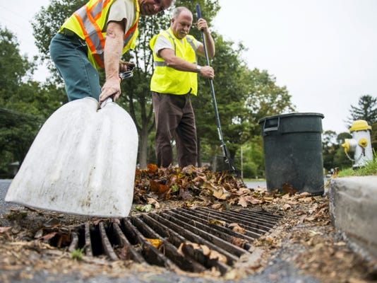 Lebanon public works employees Jeff Kleinfelter, left, and Donny Peffley clear leaves Thursday from a storm drain along Oak Street in preparation for heavy rains over the next several days.