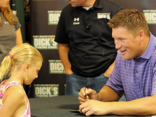 Todd Heap, former tight end for the Baltimore Ravens, signs an autograph for a young fan during a grand opening event Sunday at DICK'S Sporting Goods in Franklin Center, Chambersburg.