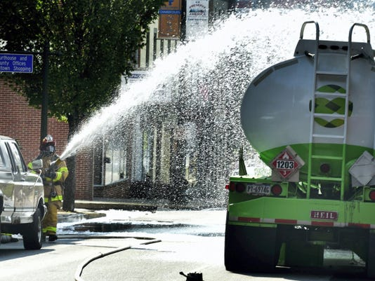 A firefighter sprays foam on the tanker truck that struck a dumpster on July 28 and leaked fuel in the first block west on Lincoln Way West, Chambersburg.