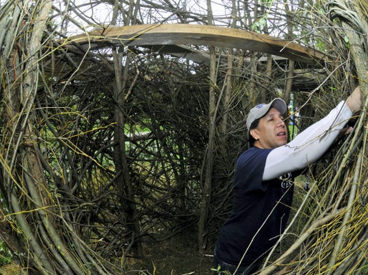 John Ross, director of major gifts at Wilson College, does his part to build the stickworks sculpture Wednesday. Renowned artist Patrick Dougherty is creating one of his world-renowned sculptures on the campus in Chambersburg. The work should be finished by Oct. 23.