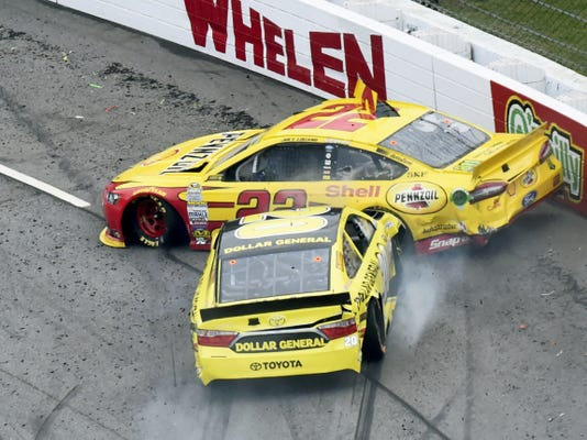 Joey Logano (22) and Matt Kenseth (20) tangle in Turn 1 during the NASCAR Sprint Cup Series race at Martinsville Speedway in Virginia on Sunday.
