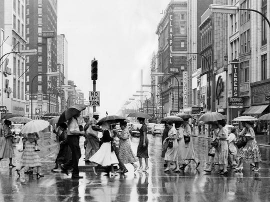 Shoppers brave the rain for Hoosier bargain day, sponsored by the downtown Merchants Association. This group of shoppers crossed Washington at Meridian streets in 1959.