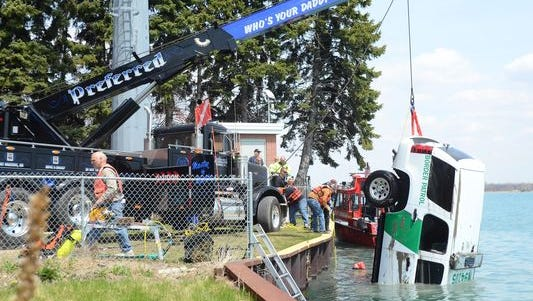 Crews work to pull a Border Patrol SUV from the St. Clair River in Algonac on April 29.
