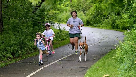 A family uses the Lansing River Trail in June. Long-term maintenance, a series of regional trail arteries and new local trails top the list of Ingham County residents' priorities as to how a parks and trails millage should be spent.