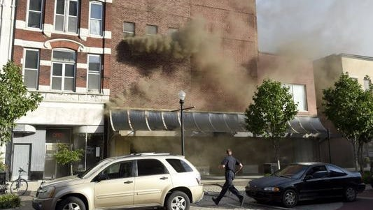 Evansville firefighters respond to a fire burning through 217 and 219 Main Street in downtown Evansville Friday. The Evansville-Vanderburgh Building Commission issued an emergency raze of the buildings.