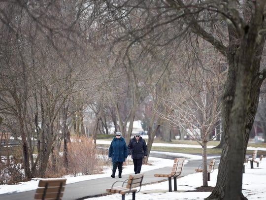 Walking is great exercise and can be done anywhere, in any season. A couple takes a walk at the Glen Rock Duck Pond at the Saddle River County Park in New Jersey.