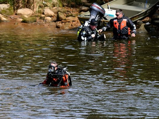 Divers head in to search the Grand River near the Brenke Fish Ladder Friday after a fisherman discovered the lower part of a human leg attached to a tennis shoe while fishing.