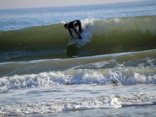 Joe Bellistri of Bethanty Beach catches a wave at the south side of Indian River Inlet on Saturday morning. Temperatures there were in the low 60s.