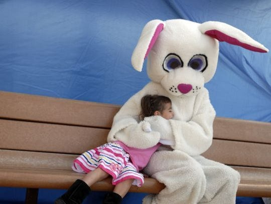 A girl hugs person dressed as the Easter Bunny during