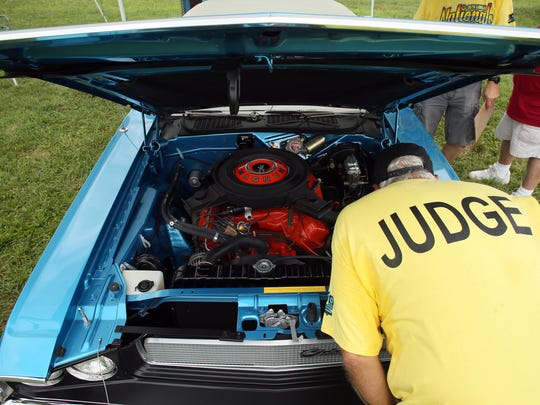 Phil Lamirand, of Cincinnati, pokes his head under the hood of Phil Dagenais' 1970 Dodge Challenger 440 R/T while judging the car show Friday afternoon during The Nationals Mopar event at National Trail Raceway.