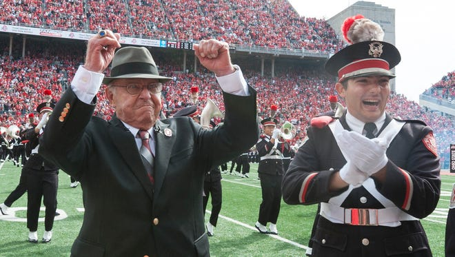 """Former Ohio State coach Earle Bruce pumps his fist after getting a chance to dot the """"i"""" in Script Ohio before a 2016 game with Rutgers."""