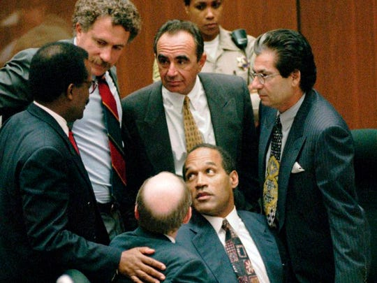 "In this Sept. 28, 1995 file photo, O.J. Simpson is surrounded by his ""Dream Team"" defense attorneys from left, Johnnie L. Cochran Jr., Peter Neufeld, Robert Shapiro, Robert Kardashian, and Robert Blasier, seated at left, at the close of defense arguments in Los Angeles."