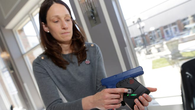 Erin Stilp, an organizer with Common Ground, shows how an Identilock  gun lock works. The lock, which requires a fingerprint to unlock it, is designed to prevent a child or thief from accessing the gun.