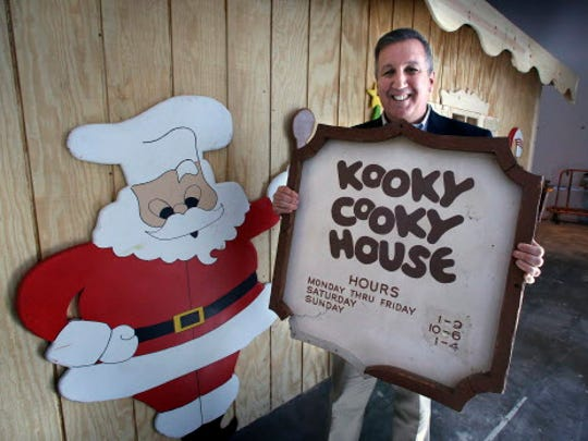 Gino Salomone holds the original sign in front of a replica of the old Kooky Cooky House.