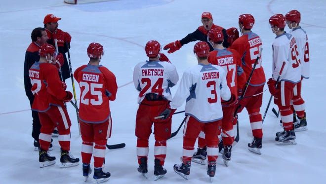 The Red Wings listen during training camp Sunday in Traverse City.
