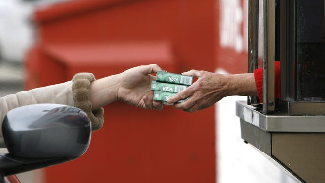 A Puff & Chew employee hands packs of cigarettes to a customer at the store off Brookville Road in Indianapolis.