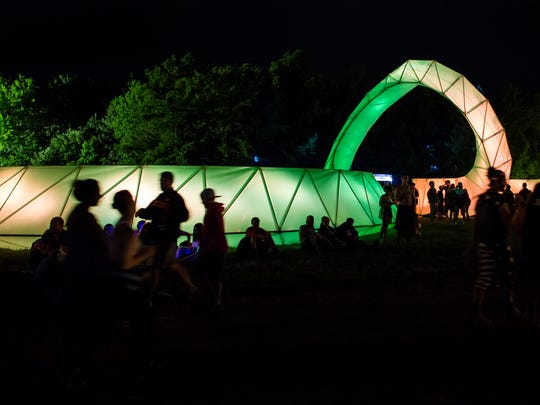 Firefly attendees gather around an art installation at the Firefly Music Festival in Dover on Thursday evening.