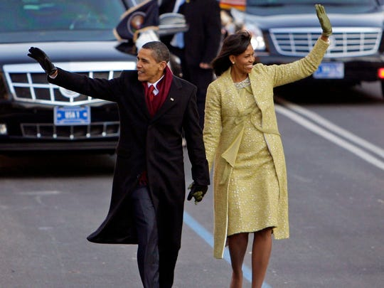 This Jan. 20, 2009, photo shows President Barack Obama with first lady Michelle Obama on their way to the White House in Washington. Obama wore a two-piece lemongrass-hued ensemble by Cuban-American designer Isabel Toledo.