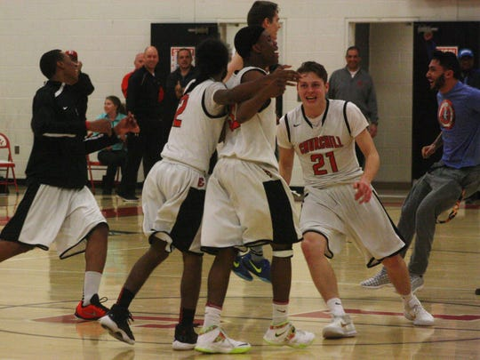Livonia Churchill basketball players celebrate after