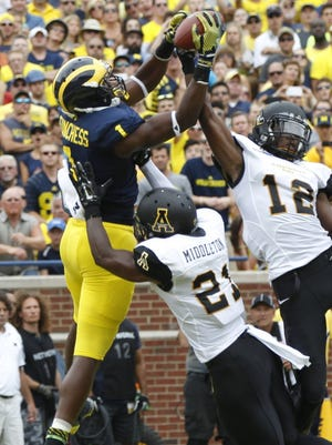 Michigan wide receiver Devin Funchess, left, outleaps Appalachian State's Doug Middleton and Jordan Ford for a touchdown in Ann Arbor on Aug. 30, 2014.