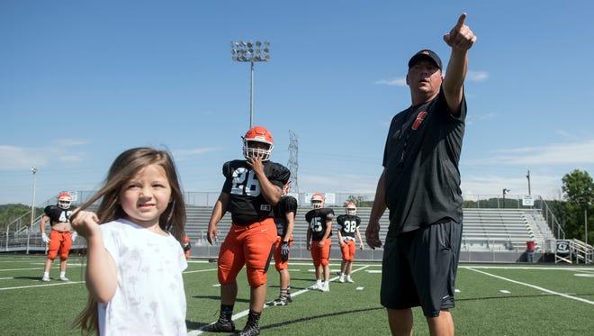 Powell football coach Matt Lowe holds practice as daughter Linni surveys the field on Thursday, May 10, 2018.