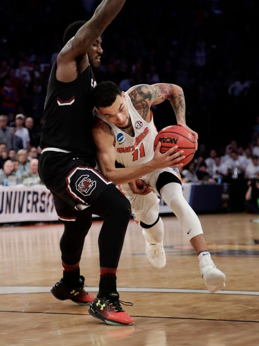 FILE - This March 26, 2017, file photo shows Florida guard Chris Chiozza (11) driving against South Carolina guard Duane Notice (10) during the second half of the East Regional championship game of the NCAA men's college basketball tournament in New York. Florida is ranked No. 8 in The Associated Press Top 25 men's college basketball preseason poll released Wednesday, Nov. 1, 2017.(AP Photo/Frank Franklin II, File)