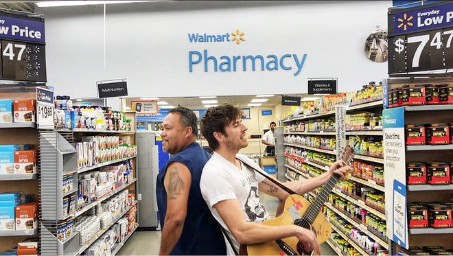 "Brett Newski (right) plays an impromptu ""dork rock bum rush"" concert at the South Milwaukee Walmart, 222 N. Chicago Ave., while a customer joins in dancing. Newski and his drummer, Spatola, were escorted from the store after a few minutes and told they couldn't film."