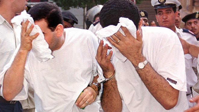 Men accused of breaking laws covering obscenity and public morality cover their faces as they enter a state security court on July 18, 2001, in Cairo.