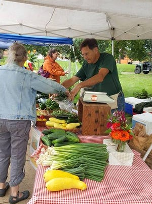 Ron Meyer of Strawberry Hill Farm assists a customer at the Coshocton Farmers Market.