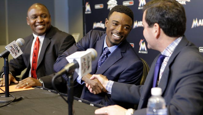 Miami Marlins second baseman Dee Gordon, center, smiles as he shakes hands with team President David Samson, right, as president of baseball operations Michael Hill, left, looks on during a news conference Monday.