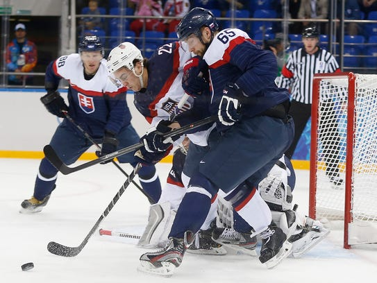 USA defenseman Kevin Shattenkirk (22) and Slovakia forward Tomas Marcinko (65) fights for control of the puck in front of the U.S. goal during the 2014 Winter Olympics men's ice hockey game at Shayba Arena, Thursday, Feb. 13, 2014, in Sochi, Russia. (AP Photo/Petr David Josek)