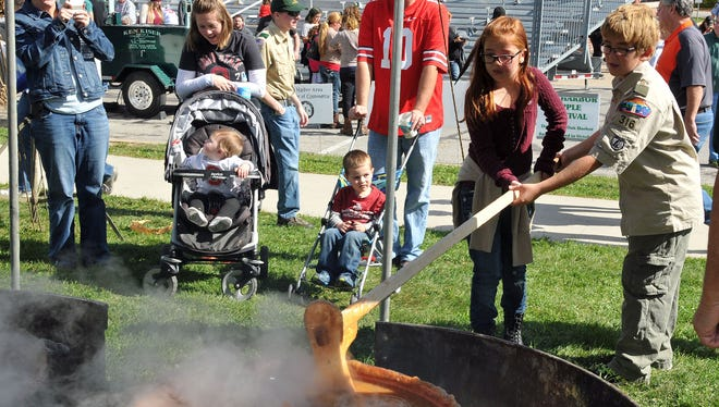 A member of Boy Scout Troop 316 of Oak Harbor and a friend churn apple butter together at the 2015 Apple Festival in downtown Oak Harbor.