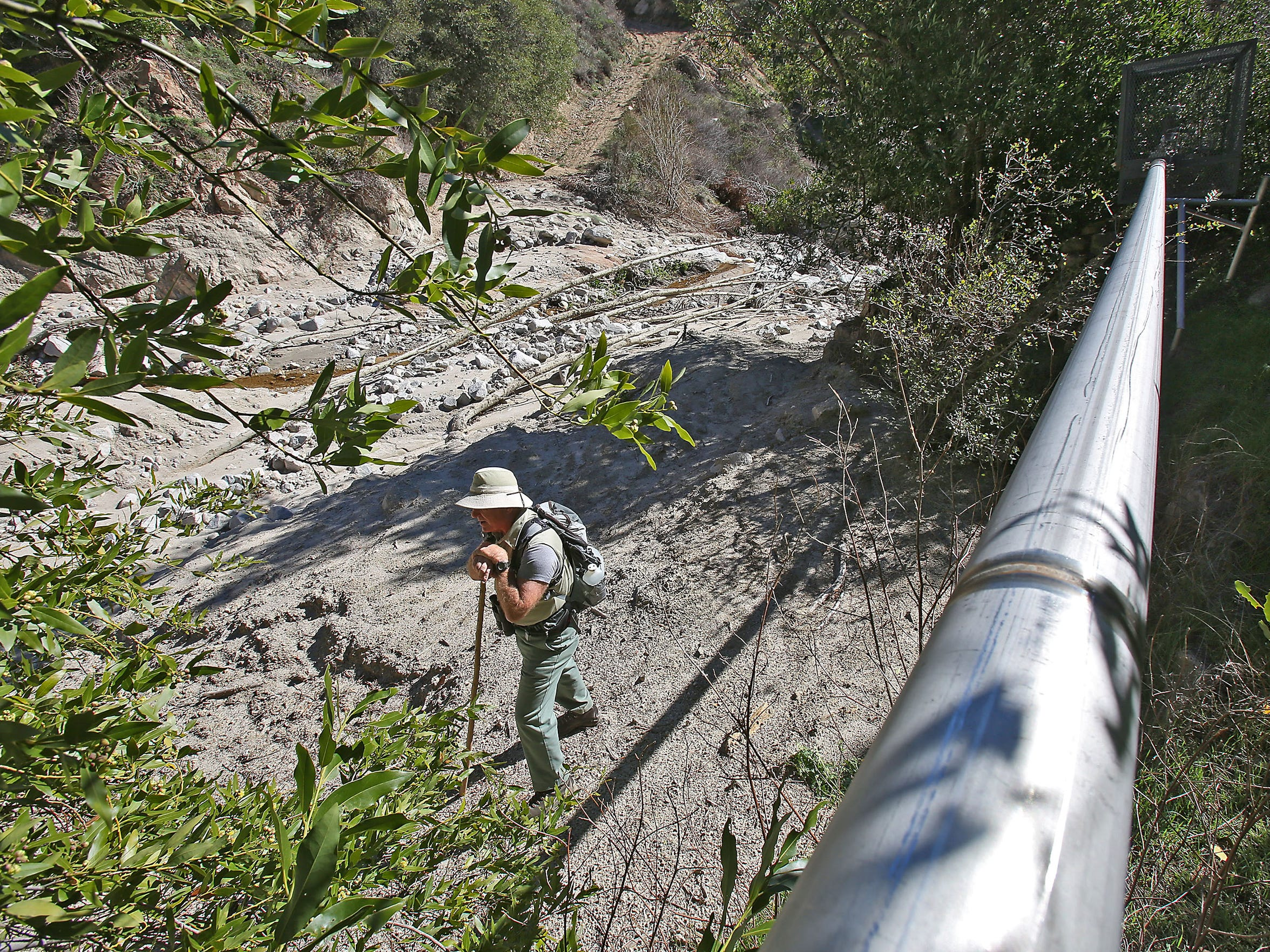 Retired Forest Service employee Gary Earney pauses with his walking stick after hiking to Strawberry Creek, where a pipe carries spring water across the national forest to be bottled.