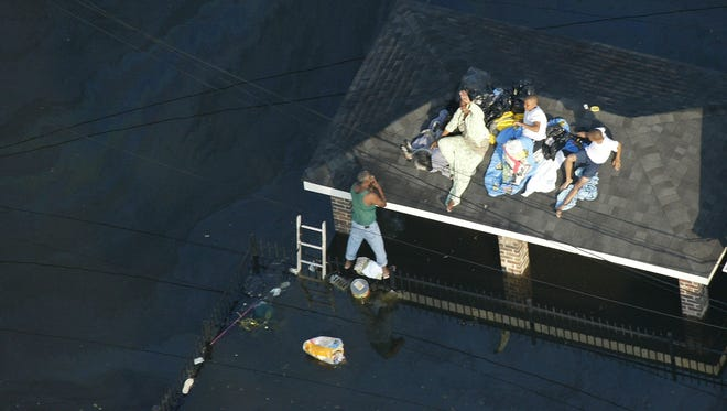 In this file photo, residents are shown in this aerial view seeking higher ground on the roof of a home as floodwaters from Hurricane Katrina covers streets Tuesday, Aug. 30, 2005 in New Orleans.