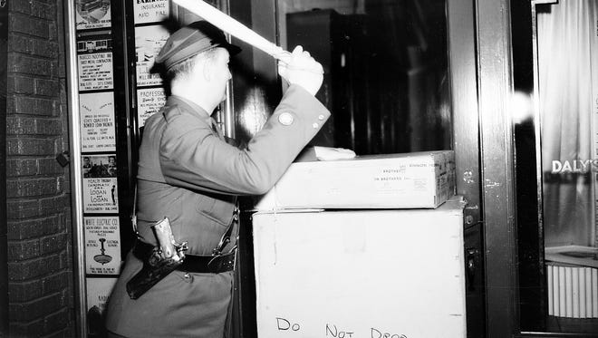 An air-raid warden made his rounds on Peoples Street, stopping to check for a light in the window of Daly's Camera Store, during a citywide blackout on Jan. 29, 1942. U-boat sightings in the Gulf, near the Aransas Pass ship channel, led to blackouts in World War II. Ships became easy targets when silhouetted against city lights.